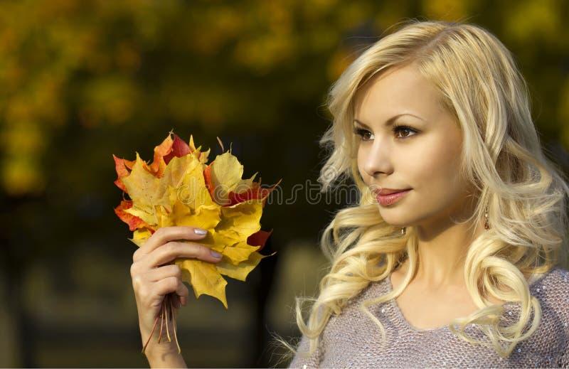 Autumn Fashion Girl. Blonde mooie jonge vrouw met gele esdoornbladeren ter beschikking. Buiten. stock afbeelding