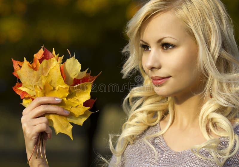 Autumn Fashion Girl. Blonde mooie jonge vrouw met gele esdoornbladeren ter beschikking. Buiten. royalty-vrije stock afbeelding