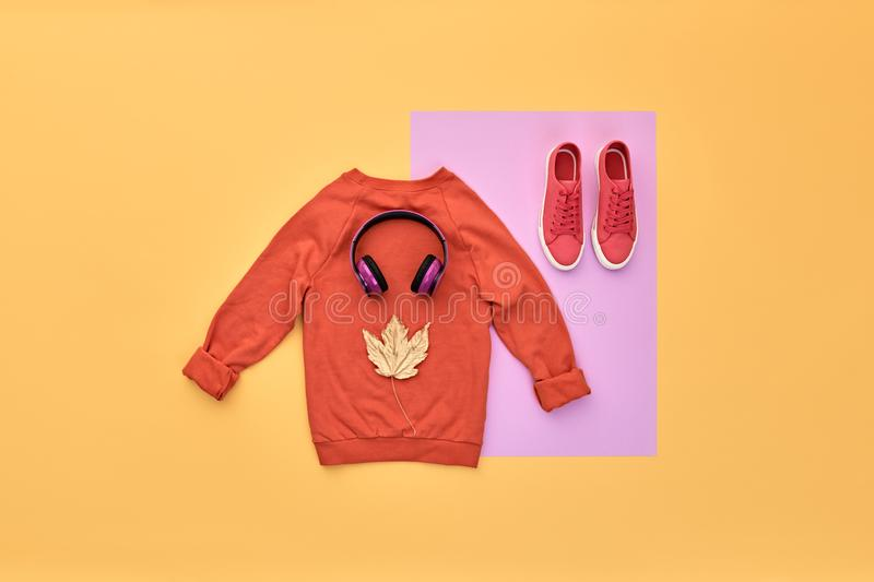 Autumn Fashion Hipster DJ Clothes Outfit Flat lay. Hipster DJ trendy colorful autumn Outfit. Fall fashion Flat lay. Orange jumper, Stylish sneakers, headphones stock image