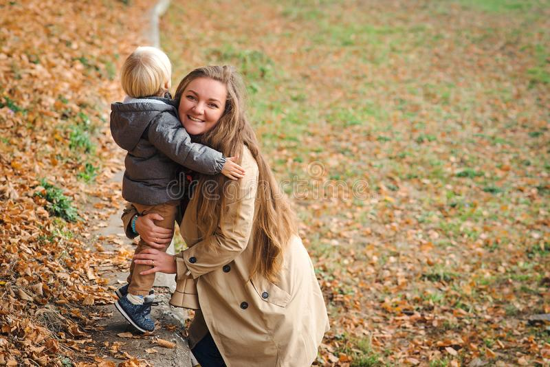 Autumn fashion, lifestyle. Young family having fun together in autumn park. Happy mother and child playing and laughing on autumn stock images