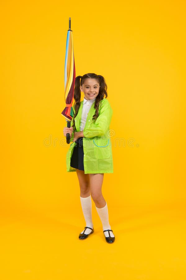 Autumn fashion. Little child in raincoat with colorful umbrella for autumn season on yellow background. Small girl stock images