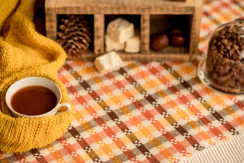 Autumn fashion seasonal concept, yellow warm soft comfortable sweater cardigan Scandinavian knitted scarf cup hot black tea coffee. Fall fallen maple leaves on royalty free stock photography