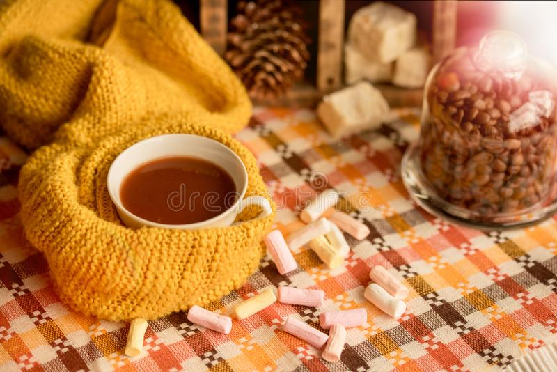 Autumn fashion seasonal concept, yellow warm soft comfortable sweater cardigan Scandinavian knitted scarf cup hot black tea coffee. Fall fallen maple leaves on royalty free stock images
