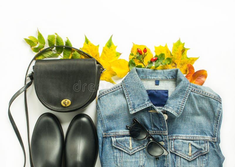 Autumn fashion, woman autumn outfit on white background. Blue denim jacket , retro sunglasses, black crossbody bag, black rain boo royalty free stock photos