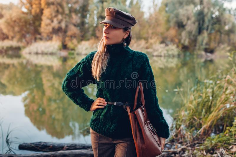 Autumn fashion. Young woman wearing stylish outfit and holding handbag outdoors. Clothing and accessories royalty free stock image