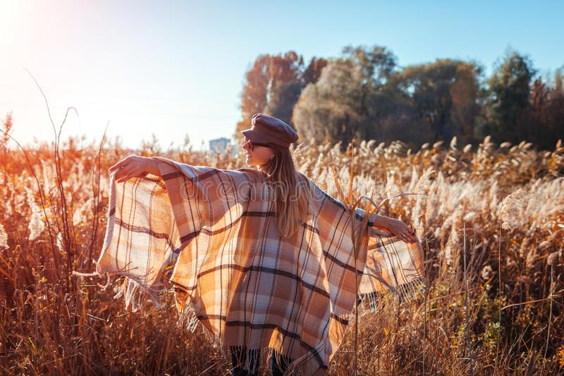 Autumn fashion. Young woman wearing stylish outfit outdoors. Clothing and accessories. Happy girl raising hands royalty free stock photography