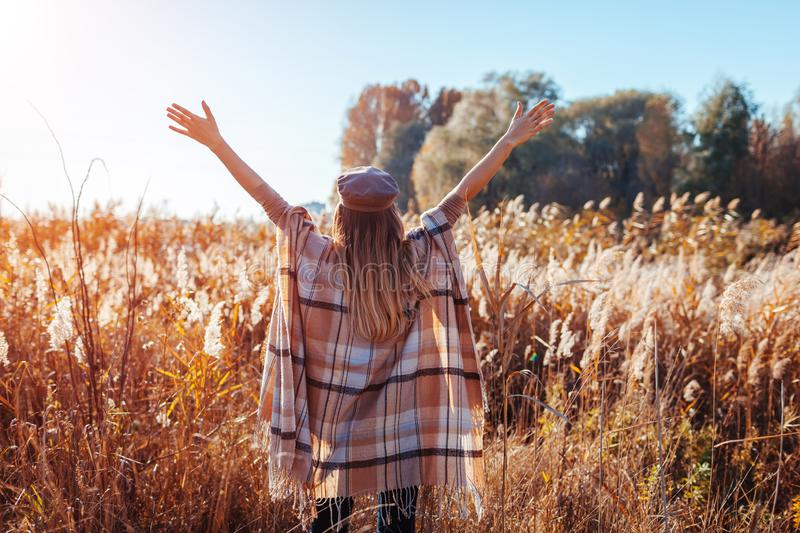 Autumn fashion. Young woman wearing stylish poncho outdoors. Clothing and accessories. Happy girl raising hands stock photography