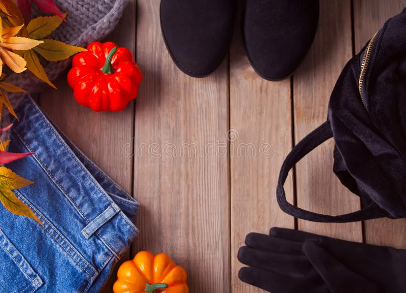 Autumn female outfit. Set of clothes, shoes and accessories on the wooden table. Top view. Copy space royalty free stock images