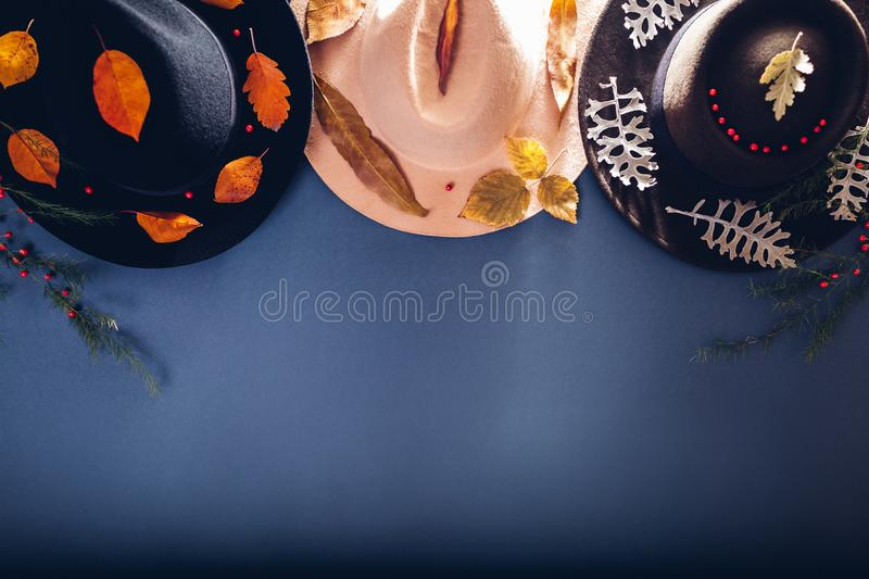 Autumn female outfit. Set of three cashmere hats decorated with fall leaves. Fashion and accessories concept. Copy space royalty free stock photo