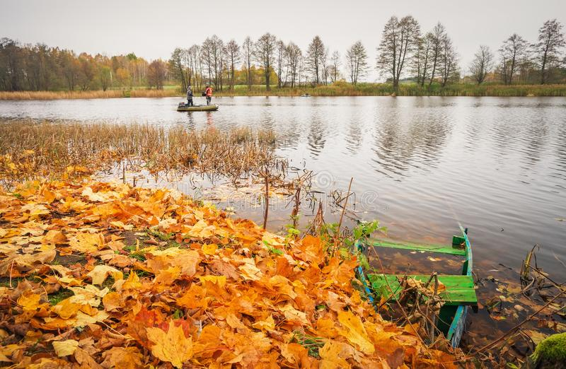 Autumn. Fall reflections in a lake with a boat royalty free stock photo