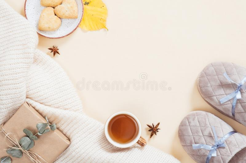 Autumn flatlay composition. Feminine desktop with white knitted plaid, gift box, slippers, tea cup, fallen leaves on pastel beige. Background. Flat lay, top royalty free stock images
