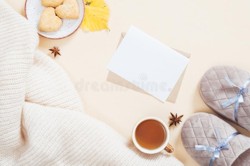 Autumn flatlay composition. Feminine desktop with white knitted plaid, letter, gift box, slippers, tea cup, fallen leaves on. Pastel beige background. Flat lay royalty free stock image