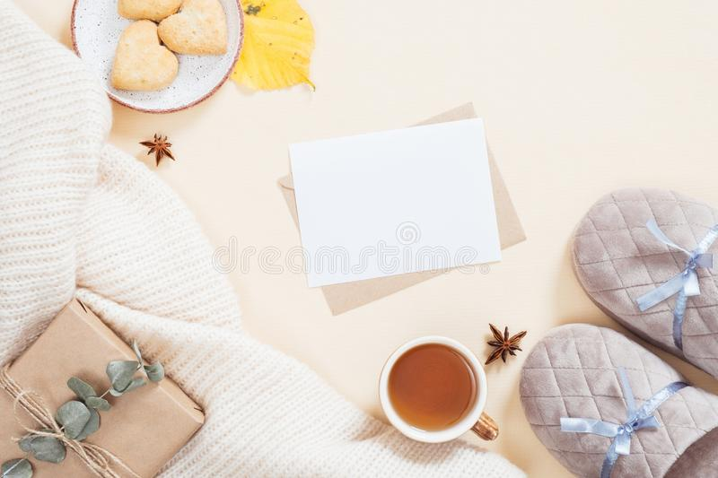 Autumn flatlay composition. Feminine desktop with white knitted plaid, letter, gift box, slippers, tea cup, fallen leaves on. Pastel beige background. Flat lay royalty free stock images