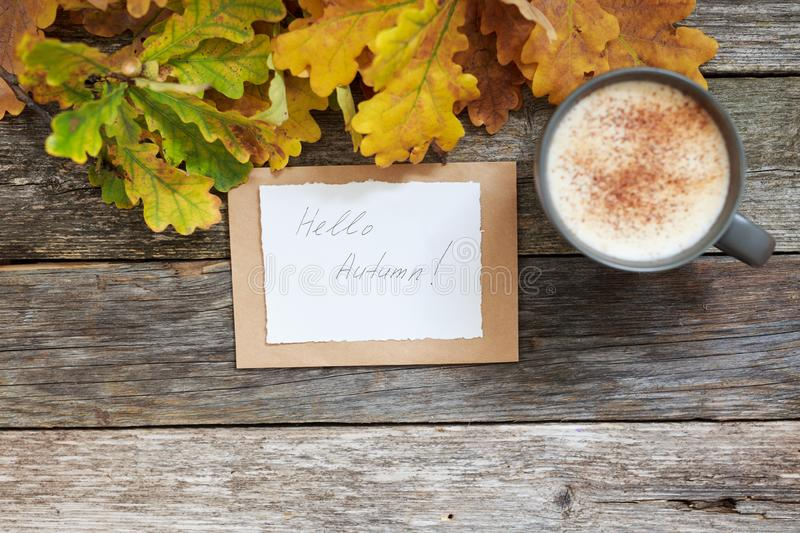 Autumn flatlay composition with letter, craft envelope, coffee latter cup mug paper card with text written Hello Autumn. Leaves, pumpkins on vintage wooden royalty free stock photo