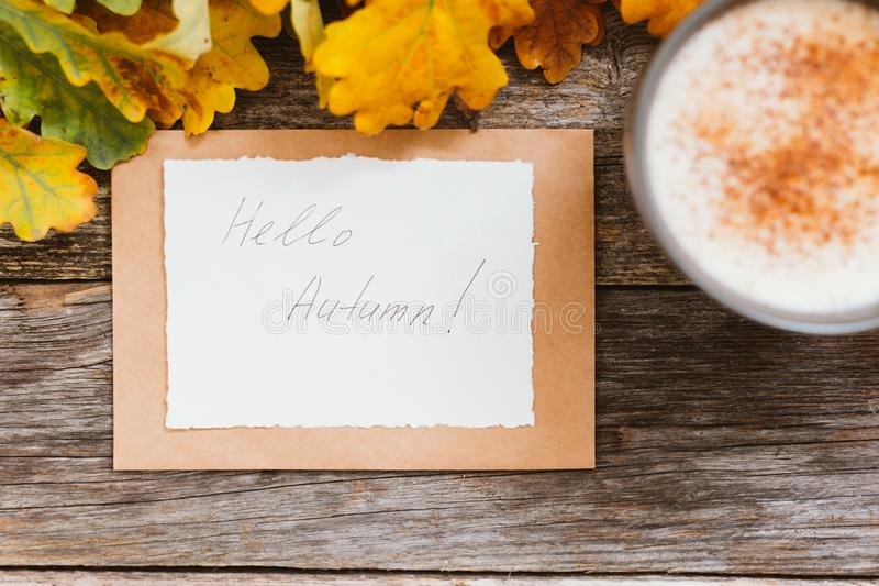 Autumn flatlay composition with letter, craft envelope, coffee latter cup mug paper card with text written Hello Autumn. Leaves, pumpkins on vintage wooden stock photos