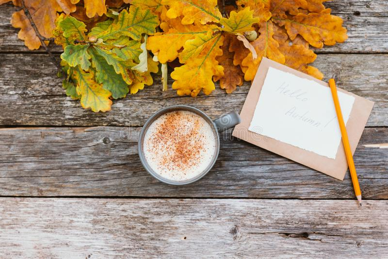 Autumn flatlay composition with letter, craft envelope, coffee latter cup mug paper card with text written Hello Autumn. Leaves, pumpkins on vintage wooden stock image