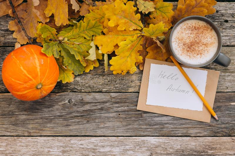 Autumn flatlay composition with letter, craft envelope, coffee latter cup mug paper card with text written Hello Autumn. Leaves, pumpkins on vintage wooden stock photography