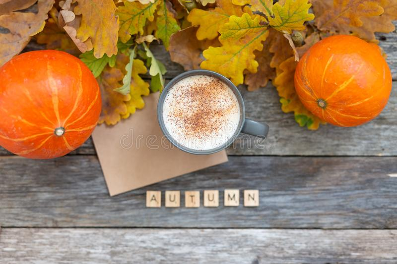Autumn flatlay composition with letter, craft envelope, coffee latter cup mug, wooden letters text Autumn, leaves. Pumpkins on vintage wooden background. Flat stock photos