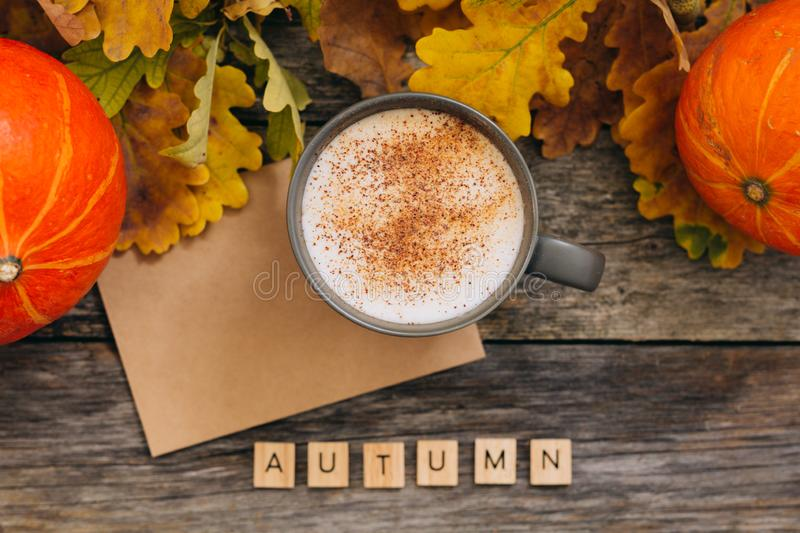 Autumn flatlay composition with letter, craft envelope, coffee latter cup mug, wooden letters text Autumn, leaves. Pumpkins on vintage wooden background. Flat royalty free stock image
