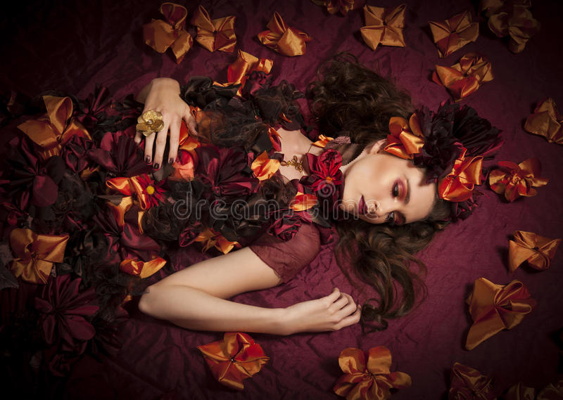 Autumn floral fantasy woman. Color portrait of a beautiful brunette woman wearing a floral fantasy outfit of autumn colors, red and gold makeup, lying amidst stock photos