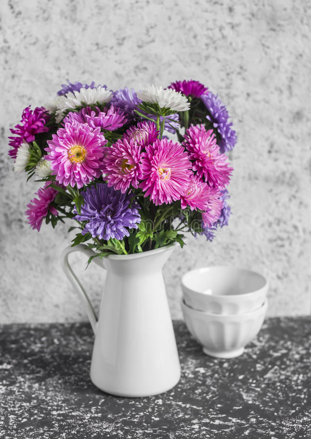 Autumn flowers asters in a white pitcher on a light background. stock photo