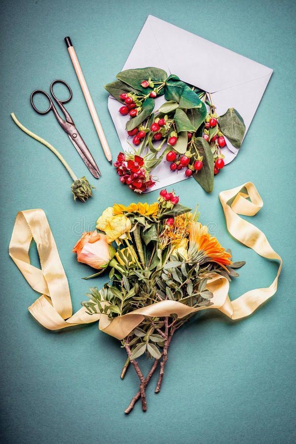 Autumn flowers bunch with envelop , shears , pencil and flowers on blue workspace table background, top view. Creative Flowers ar stock photos