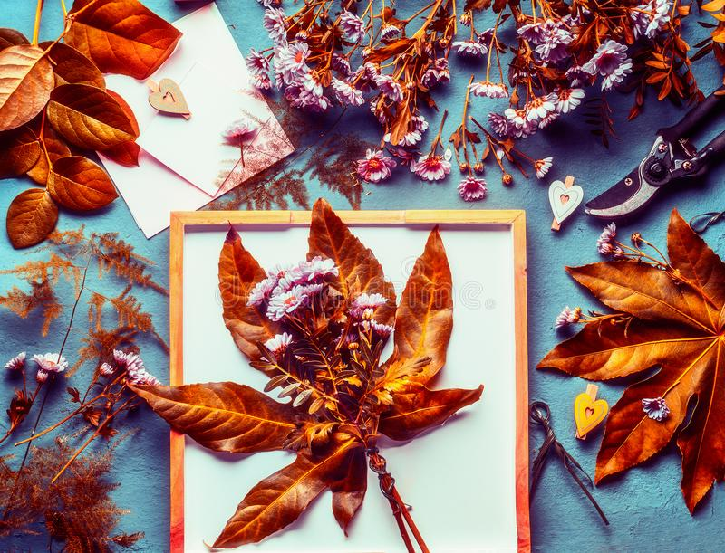 Autumn flowers bunch with orange leaves and chrysanthemum on desktop background with decoration and florist tools. For fall arrangement , top view royalty free stock photography