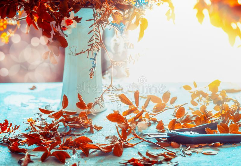 Autumn flowers bunch and vase on blue table with sunshine. Cozy home interior decoration. Fall still life. Front view stock image
