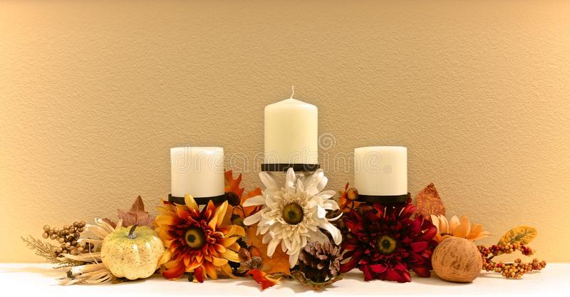 Autumn flowers candelabra. Fall autumn colored flowers of orange cream and yellow decorate black candelabra centerpiece with white candles stock photo