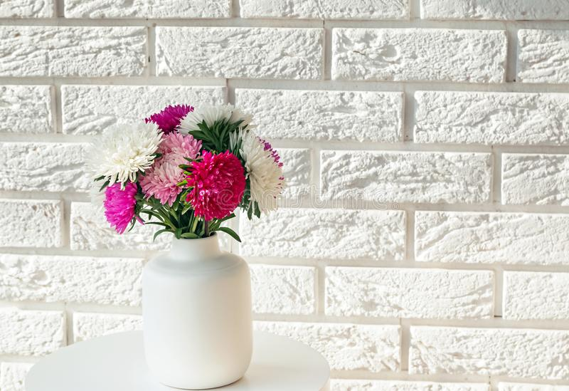 Autumn flowers of pink, white and purple colors standing on the small table stock photography