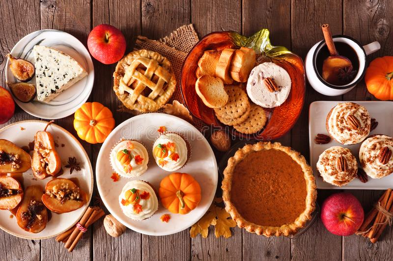 Autumn food table scene with pies, appetizers and desserts. Above view over a rustic wood background. royalty free stock photos