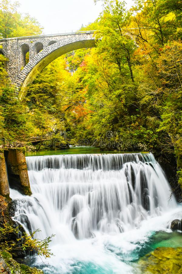 Autumn forest colors with turquoise waterfall and old rocky train bridge in natural park. Of Vintgar river gorge Slovenia stock photos