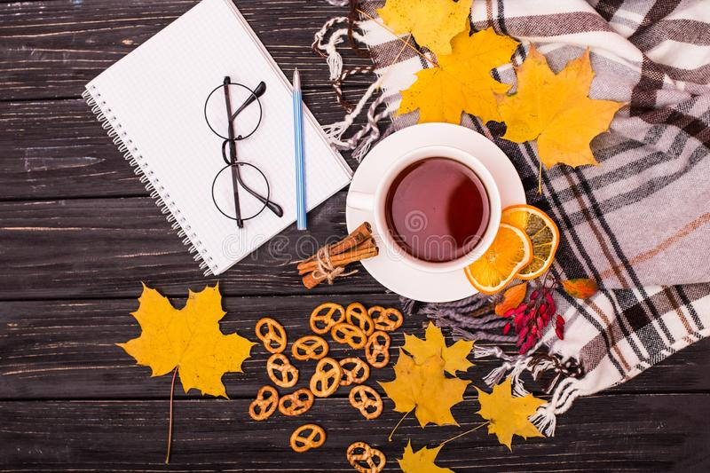 Autumn frame flat lay composition on a wooden background. Maple leaves, season tea, open notebook with empty sheets and warm scarf. Autumn frame flat lay royalty free stock image