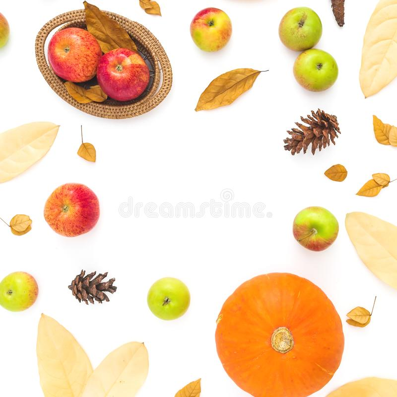 Autumn frame made of fall leaves, pine cones, apples and pumpkin on white background. Thanksgiving day. Flat lay, top view. Autumn frame made of fall leaves royalty free stock images