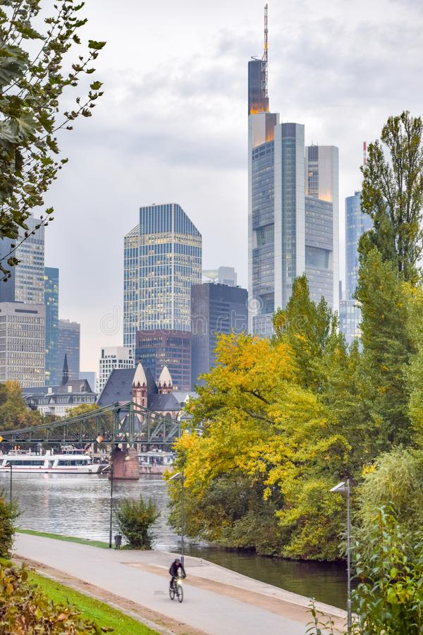 Skyline of Frankfurt and Riverside Park at Dusk. Autumn in Frankfurt: Vertical Shot of Walking and Bike Paths in Urban Riverside Park, with the Skyline of stock photography