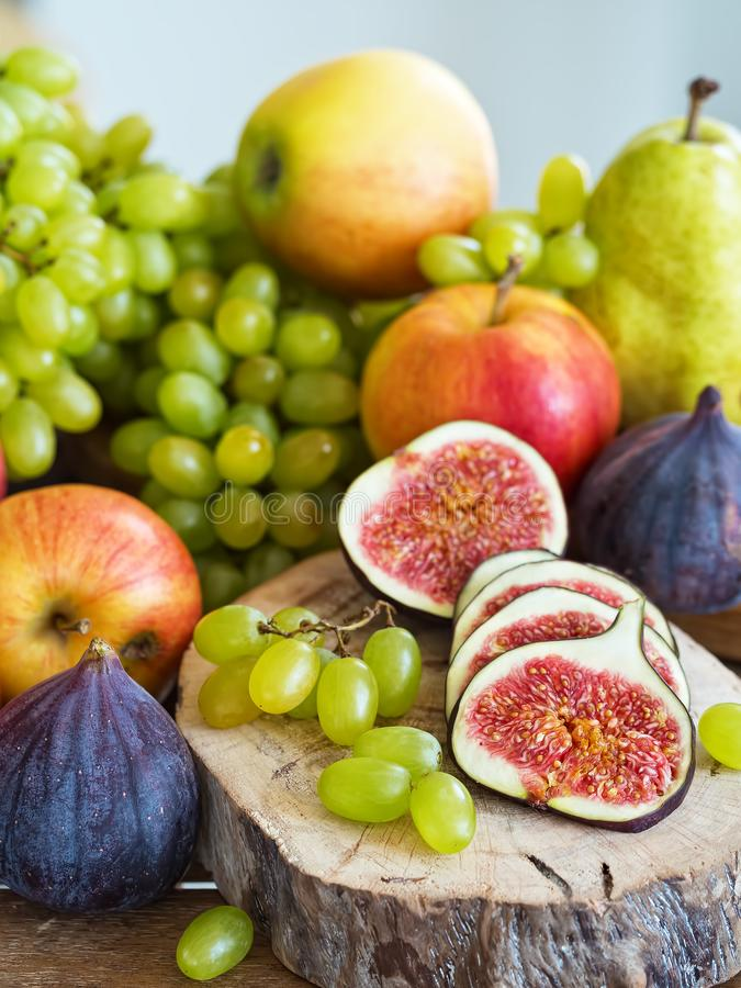 Autumn, fresh fruits. In the foreground, sliced figs located on a wooden tray. Close-up. Autumn, fresh fruits. In the foreground, sliced figs located on a wooden stock photos