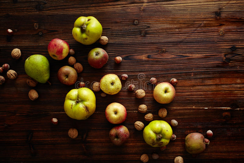 Autumn fruits on wooden table. Quinces walnuts hazelnuts apples pears on dark wood atmosphere and perspective from above royalty free stock images