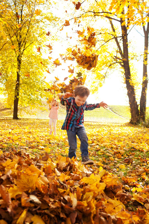 Autumn fun. Image of boy and girl playing with autumn leaves in the park, shallow depth of field stock photo