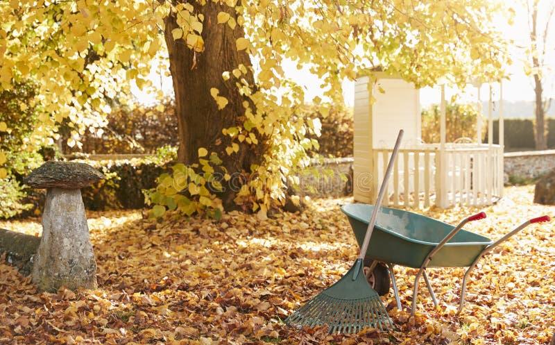 Autumn Garden Scene With Rake und Schubkarre lizenzfreie stockfotos
