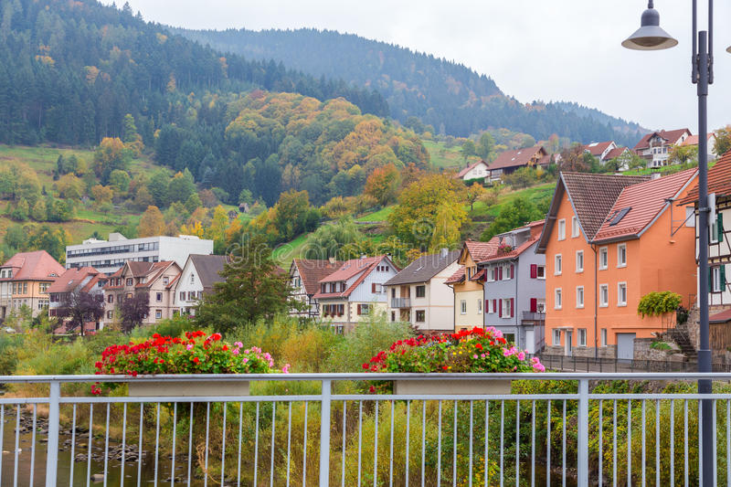 Autumn Gernsbach city landscape in Germany. Autumn city landscape with hills and blossoming geranium on Murg river bridge in Gernsbach, Germany stock image