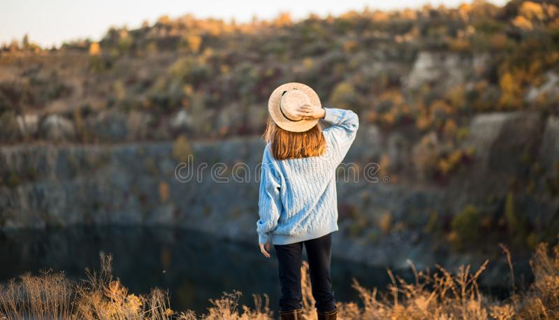 Autumn girl in blue sweater and hat standing backwards and admire nature lake view. Autumn colors with girl back view. royalty free stock images