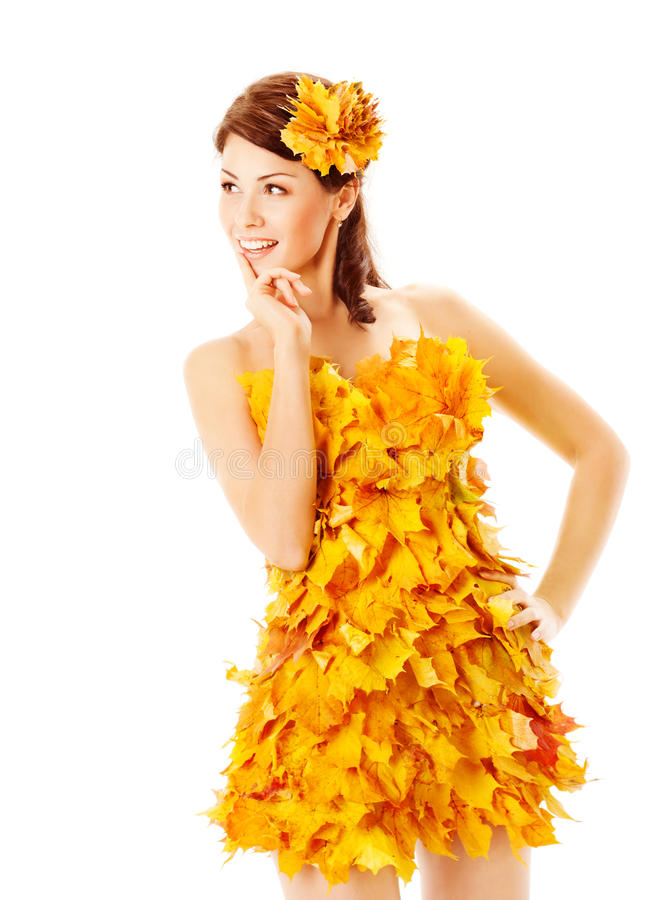 Autumn girl in dress of maple leaves over white. Autumn woman in fashion dress of maple leaves holding bouquet of maple leaves. White background royalty free stock photos