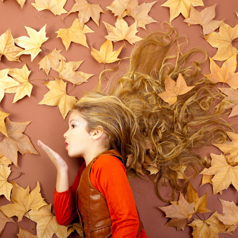 Autumn girl on dried leaves blowing wind lips. Autumn fall little blond girl on dried tree leaves blowing wind with lips royalty free stock photography