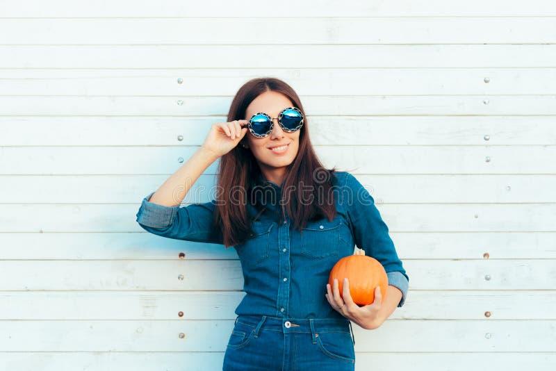 Autumn Girl frais dans l'équipement et des lunettes de soleil de denim tenant le pompage image stock