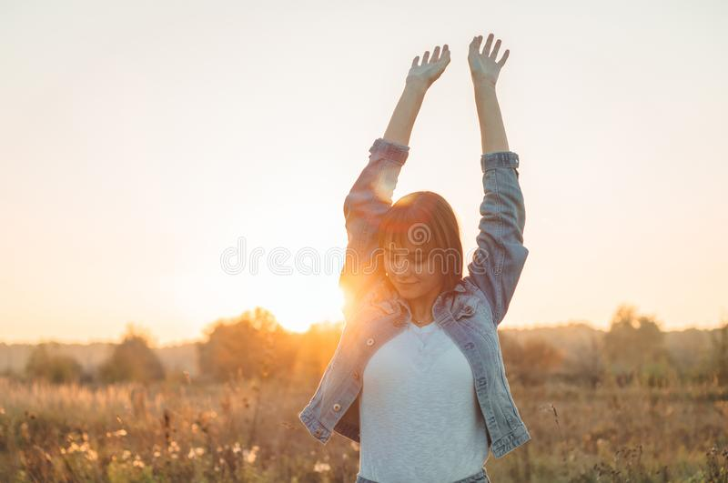 Autumn Girl que aprecia a natureza no campo A menina da beleza que levanta fora as mãos na luz solar irradia Menina modelo adoles fotografia de stock