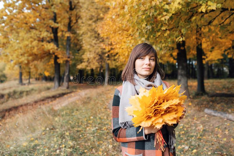 Autumn girl walking in city park. Portrait of happy lovely and beautiful young woman in forest in fall colors. stock image