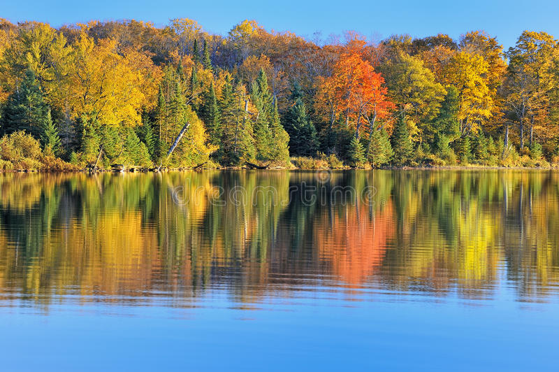 Autumn at Grand Sable Lake. As the sun drops behind Grand Sable Dunes, it casts a beautiful Fall reflection on the shores of Grand Sable Lake. Pictured Rocks royalty free stock photo