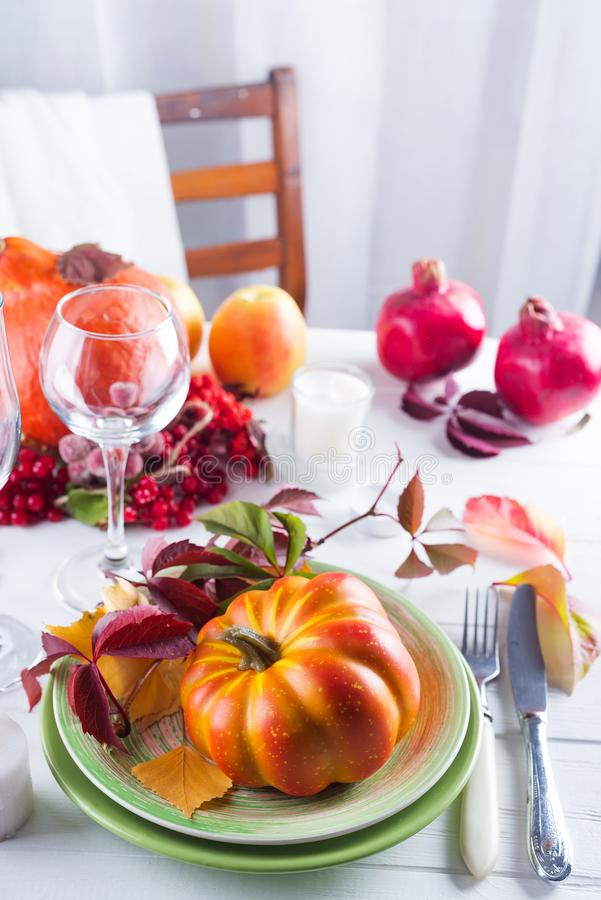Autumn Halloween or thanksgiving day table setting. Fallen leaves, pumpkins, spices, empty plate and cutlery on wooden royalty free stock images