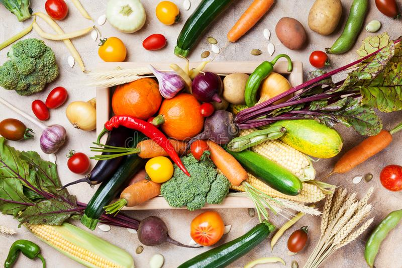 Autumn harvest farm vegetables and root crops on wooden box top view. Healthy and organic food. Autumn harvest farm vegetables and root crops on wooden box from royalty free stock image