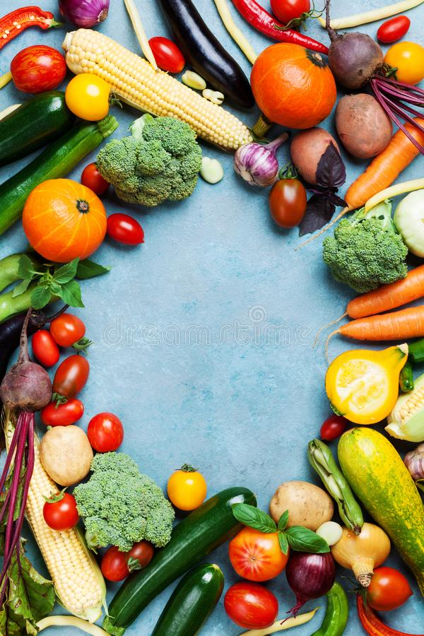 Autumn harvest of organic root and farm vegetables on blue table top view. stock photos